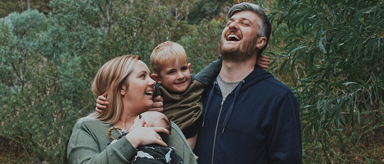 A family laughing and smiling while on a walk.