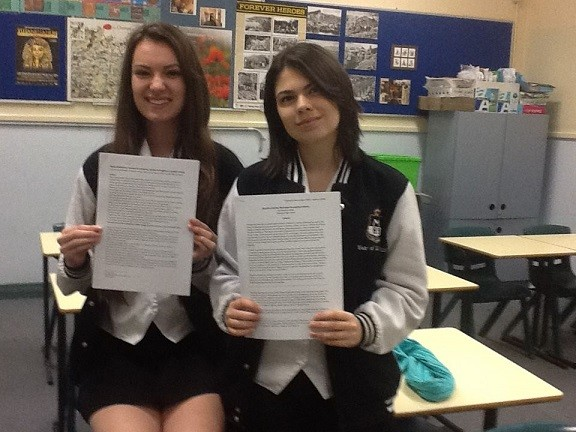 Two students holding reports