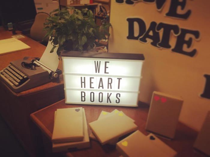 Desk with an electronic poster that says we heart books